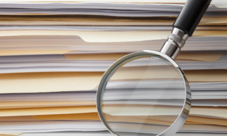 Magnifying glass against stack of documents