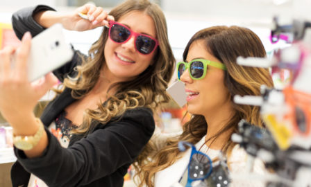 Two women shoppers in a store using snapchat while trying on sunglasses