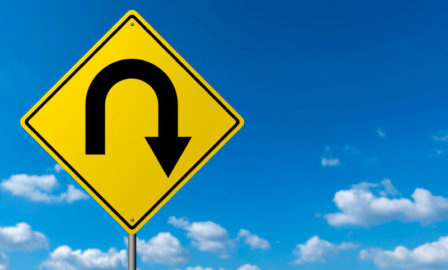 Image of a turn around sign against a blue sky